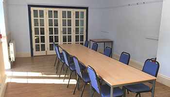 A picture of long meeting table with multiple chairs around it.