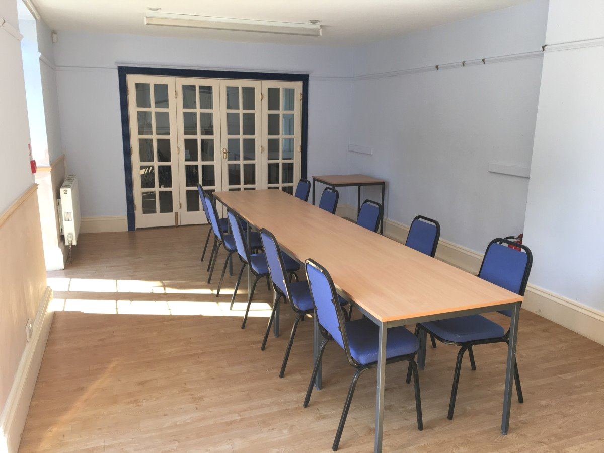 A picture of another angle, of the long meeting table with many chairs around it.