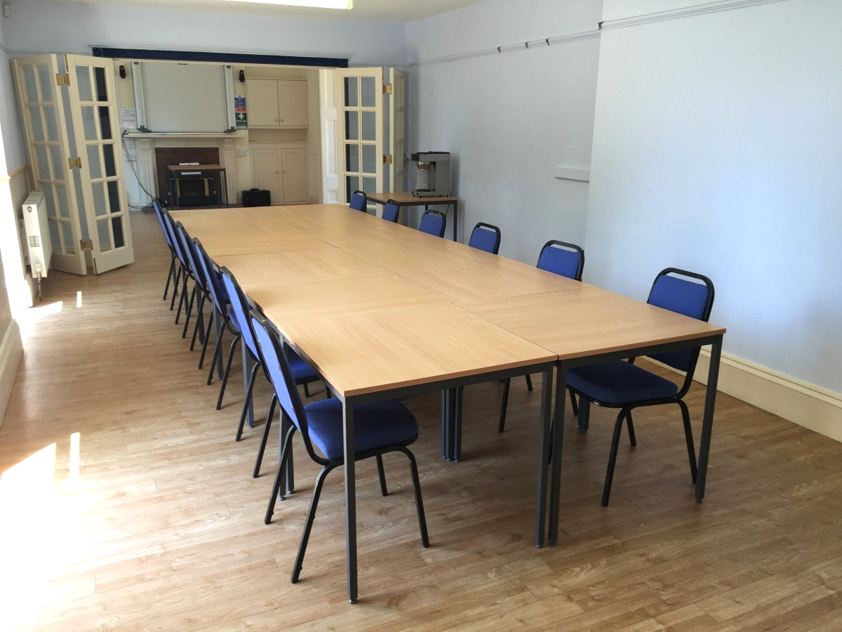 A picture of a long meeting table with many chairs around it.