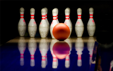 A picture of a bowling ball, rolling down the alley.