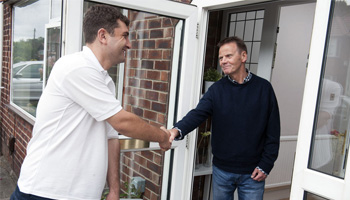A picture of a man shaking hands with another man at his doorstep.