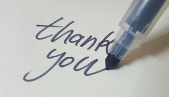 "A picture of a felt tip pen, writing the words ""thank you""."