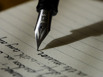 A picture of a fountain pen writing on paper.