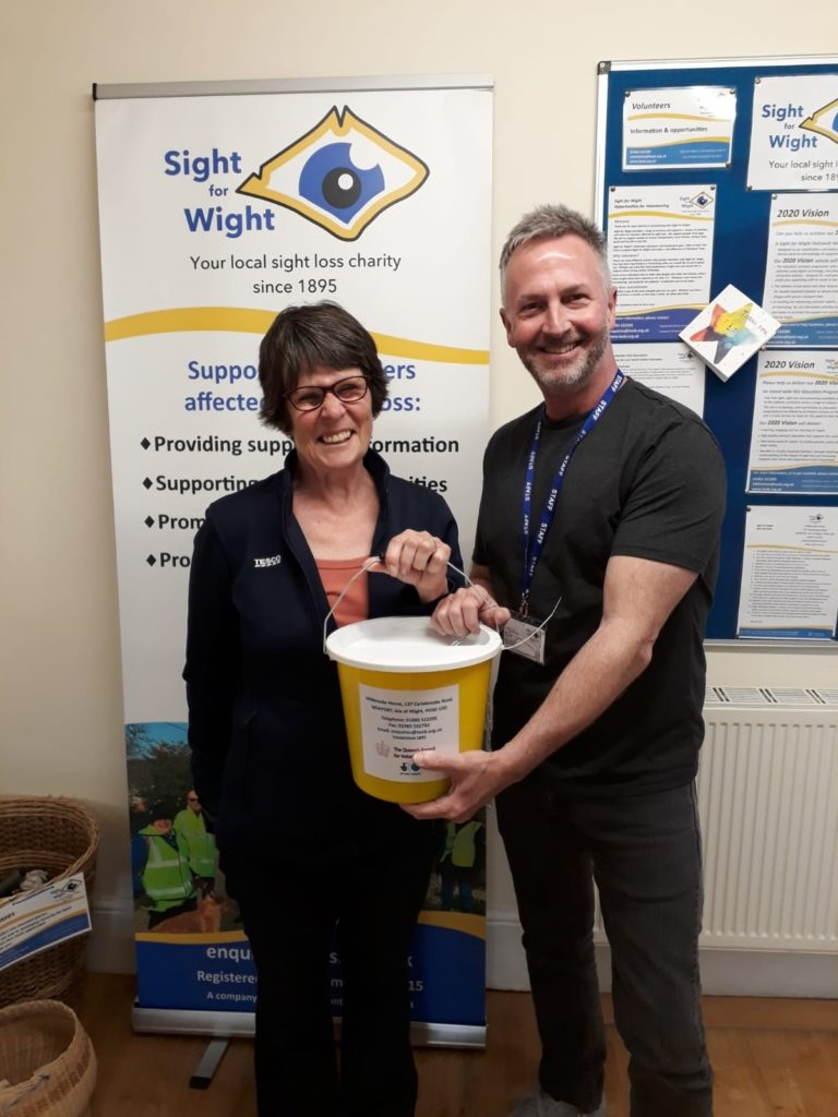 Jan Gibson at TESCO handing over the cash raised from sale of cassette tapes to Chris Cane, Marketing, Communications & Fundraising Manager