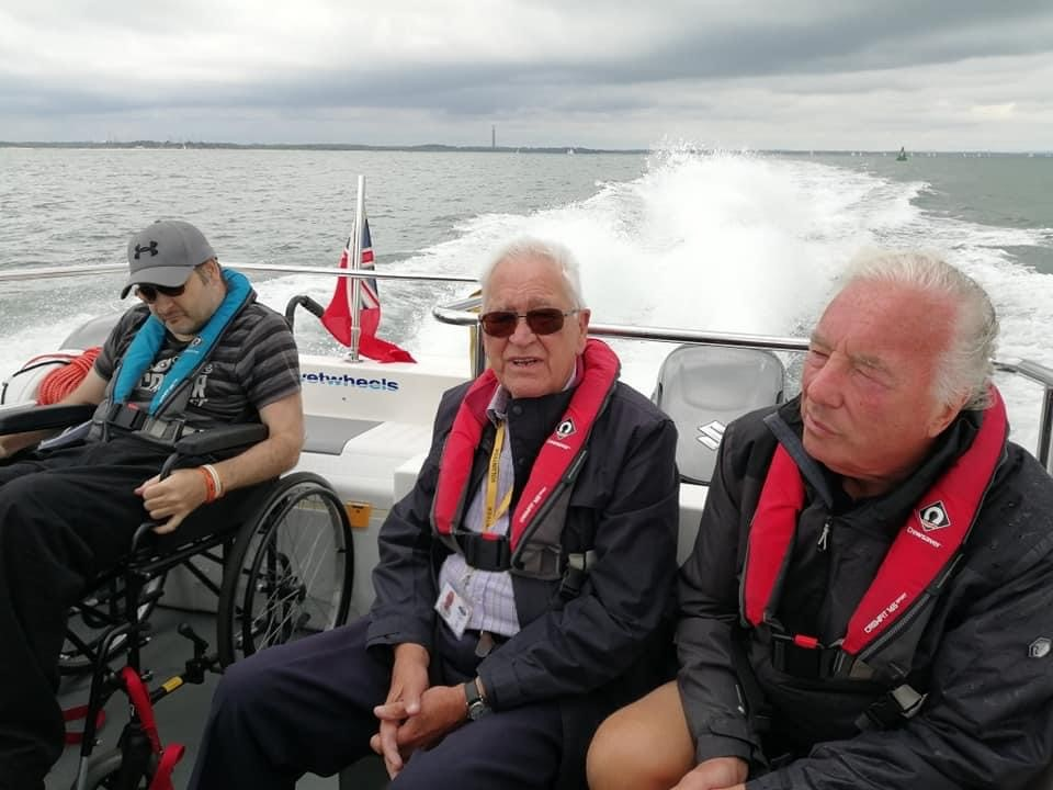 Alan, our volunteer, sits with two members out on the boat.