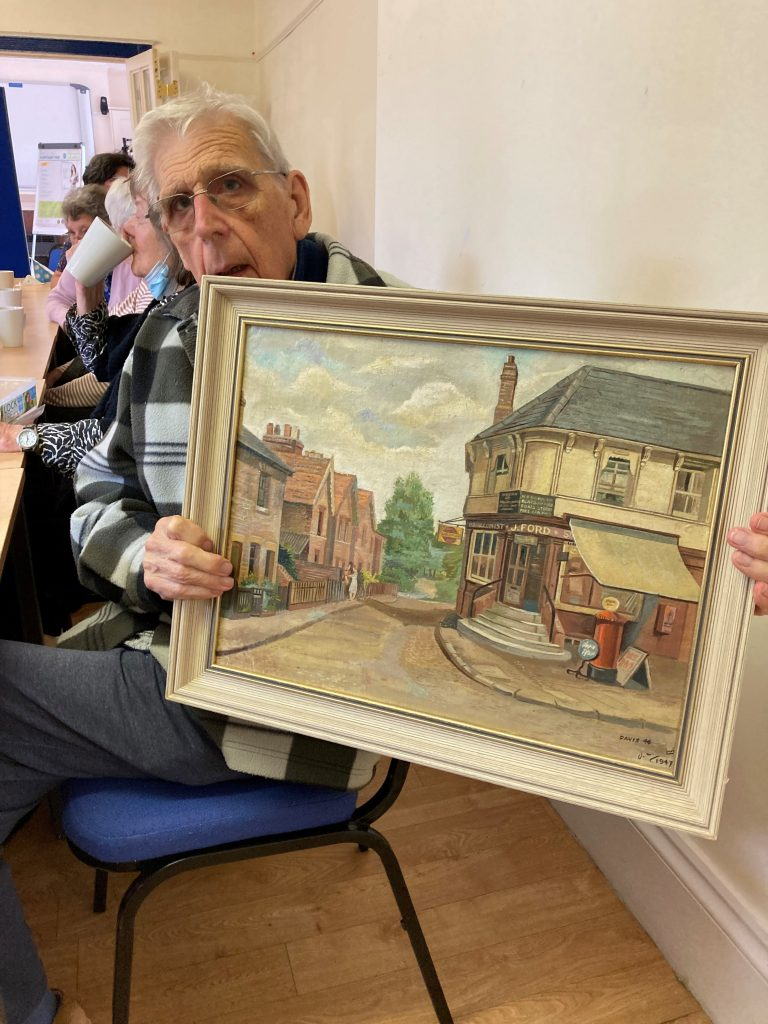 Our member John showing a painting he did of a village.